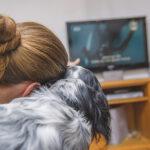 Mulher vendo filme de cachorro com o pet