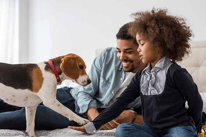Pai e filha com um cachorro beagle