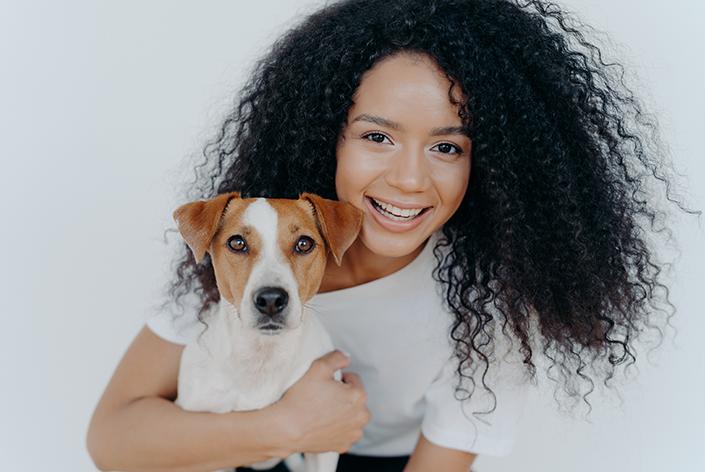 cachorro bicolor sendo abraçado por mulher de camiseta