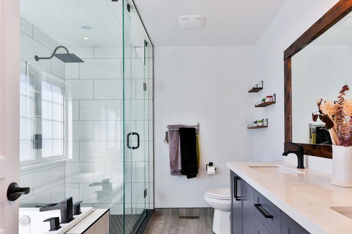 Decoração para banheiros pequenos e bonitos com espelho grande, nichos sobre a privada e plantas no gabinete